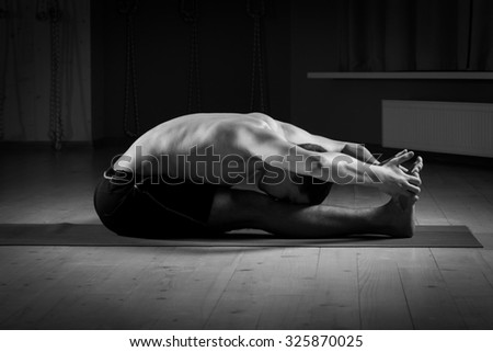 young man practicing yoga in sports hall - stock photo