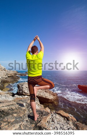Young man practicing yoga on the beach. - stock photo