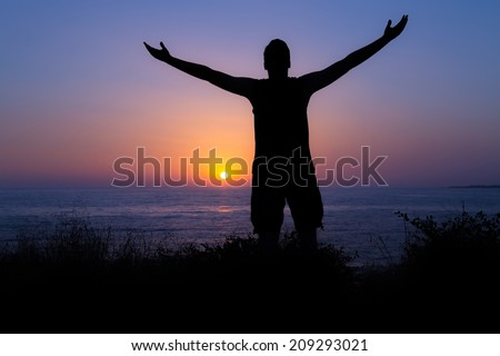 Young man praising and worshiping God during sunset by the sea - stock photo