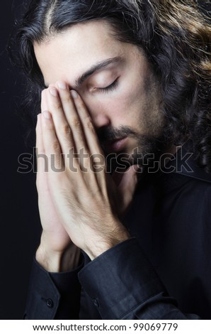 Young man praying in darkness - stock photo