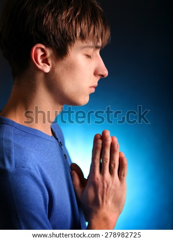 Young Man Praying in the Dark Room - stock photo
