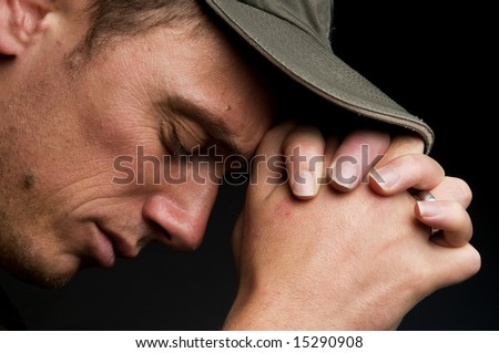 Young man praying, on a black background. - stock photo