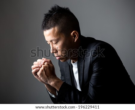 Young man praying to god - stock photo