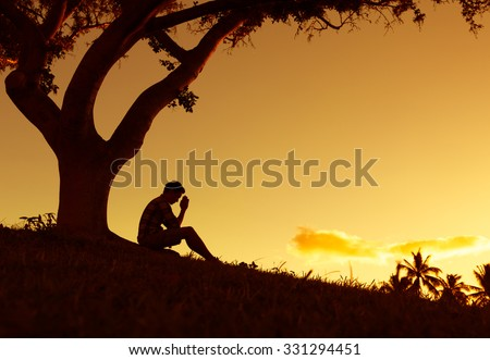 Young man praying under a tree.  - stock photo