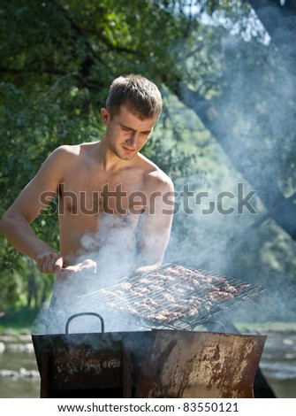 Young man preparing barbecue outdoors