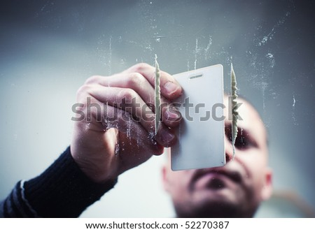Young man preparing cocaine lines. - stock photo