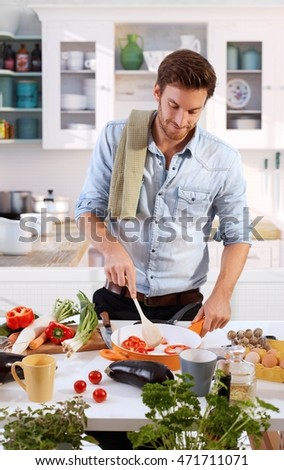 Young man preparing food at home in kitchen.
