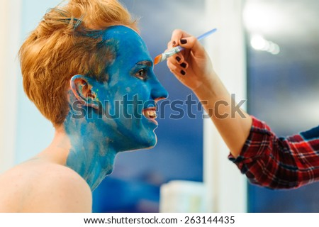 Young man preparing for photosession with bodyart painting in studio, backstage - stock photo