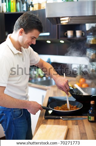 Young man preparing lunch in kitchen - stock photo