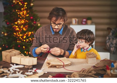Young man preparing thread for tying xmas gifts with his son near by - stock photo