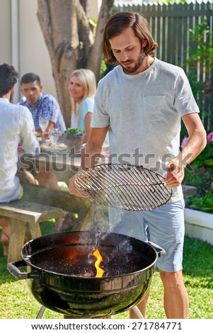 young man preparing to grill on fire for friends outdoor barbecue garden party - stock photo