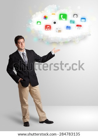 Young man presenting cloud with colorful app icons and symbols concept - stock photo