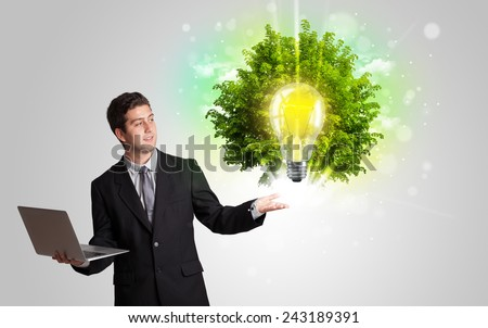 Young man presenting idea light bulb with green tree concept - stock photo