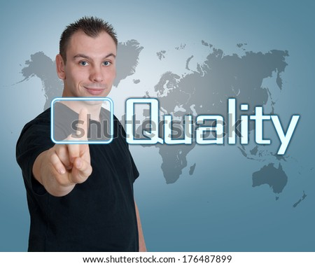 Young man press digital Quality button on interface in front of him - stock photo