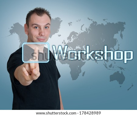 Young man press digital Workshop button on interface in front of him