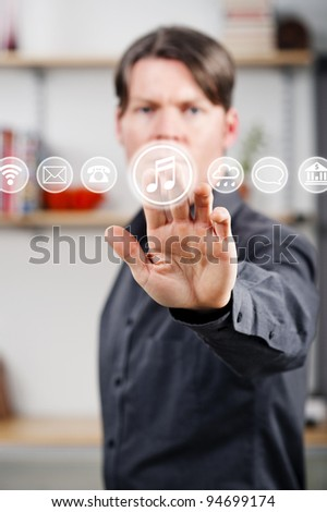 young man pressing a digital music button on a virtual touch screen
