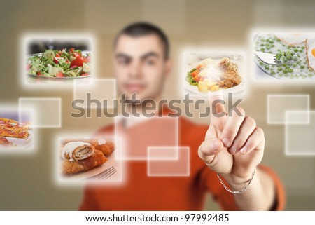 Young man pressing a touchscreen button, with food selection - stock photo