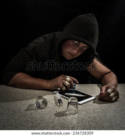 young man pretending to be a drug addict for a concept image using a syringe, shot glasses and white powder - stock photo