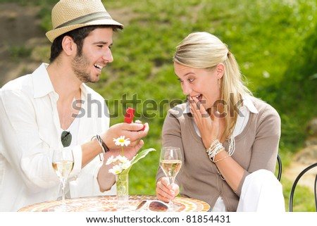 Young man proposing to girlfriend offering engagement ring sunny terrace - stock photo