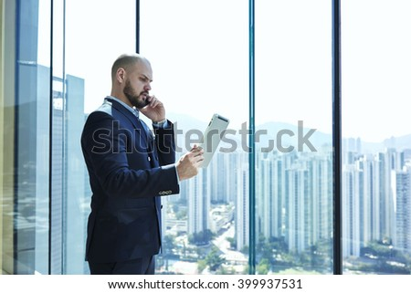 Young man proud CEO is analyzing activity of the company via digital tablet and talking with financial manager during his business trip in China, while is standing near office window with copy space - stock photo