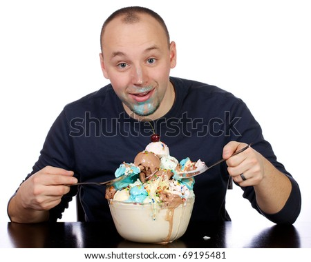 Young man proudly prepares to dive into his giant bowl of ice creak with two big spoons. - stock photo