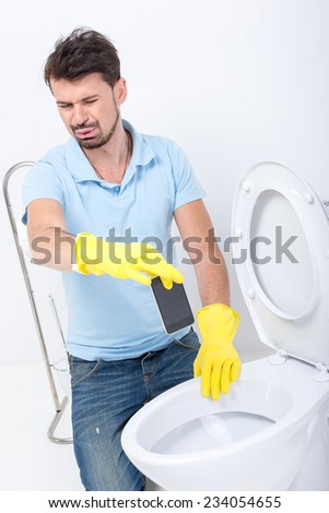 Young man pulled the phone from the toilet. - stock photo