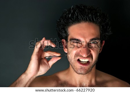 Young man pulling his beard with tweezers - stock photo