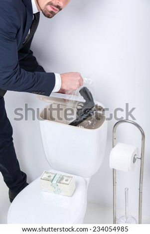 Young man pulls gun from the toilet tank. - stock photo
