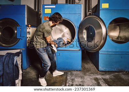 Young man pulls out his girlfriend from a large industrial washing machine, funny couple moments - stock photo