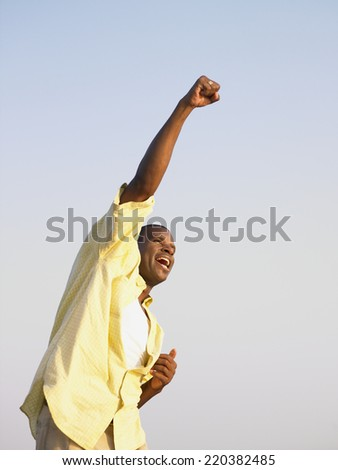 Young man punching the air in triumph - stock photo