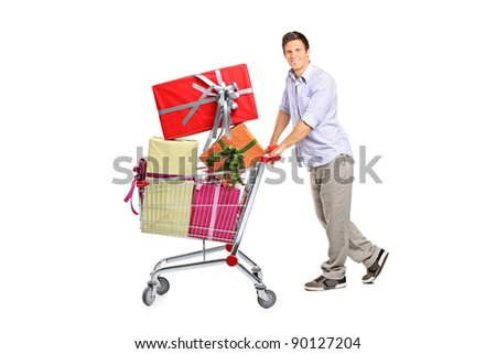 Young man pushing a shopping cart full with gifts isolated against white background - stock photo
