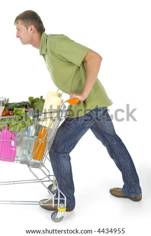Young man pushing full of things trolley. Looking tired. Side view - stock photo