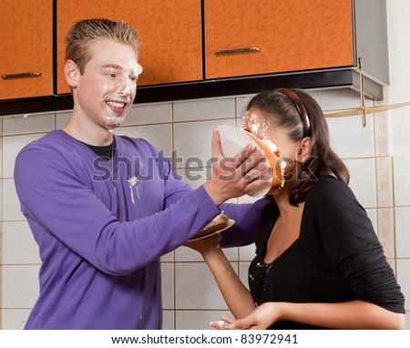Young man putting a cream pie in his girlfriend's face - stock photo