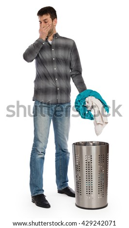 Young man putting a dirty towel in a laundry basket, isolated