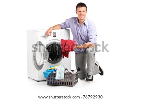 Young man putting clothes into washing machine and smiling isolated on white background - stock photo
