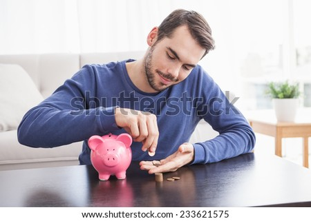 Young man putting coins in piggy bank at home in the living room - stock photo