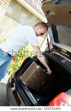 Young man putting his baggage in open trunk of car - stock photo