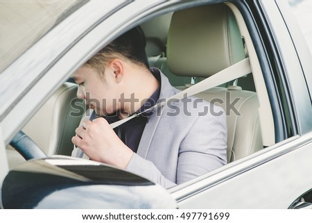 Young man putting his seat belt in car.