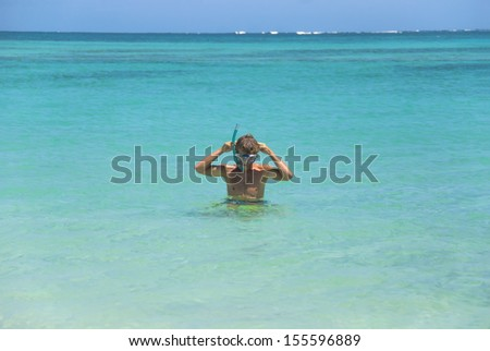 Young man putting on snorkeling gear. Exmouth, Western Australia - stock photo