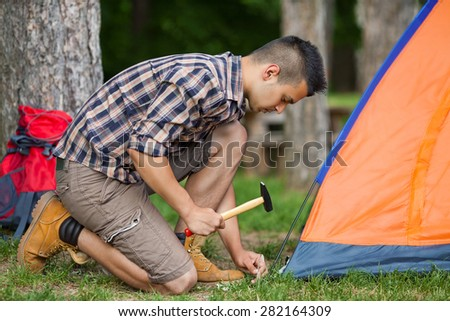 Young man putting up a tent