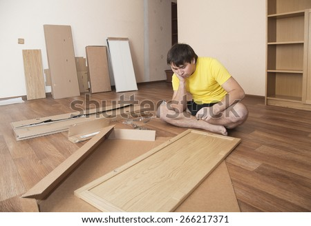 Young man puzzled about assembling flatpack closet - stock photo