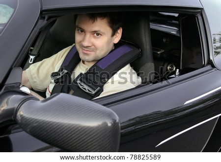 Young man, racer sitting in sport black car and looking from opened window with smiling