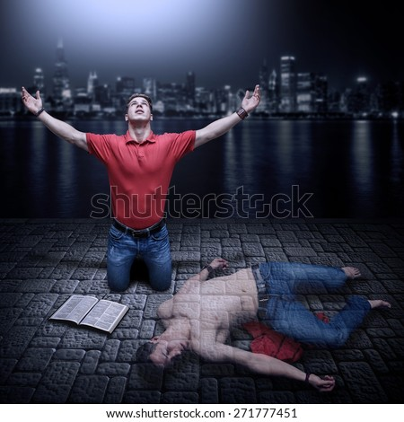 Young man raised in prayer with a Bible beside him. Concept for a young man dead in his sins and resurrected by the power of God through prayer and Word of God. - stock photo