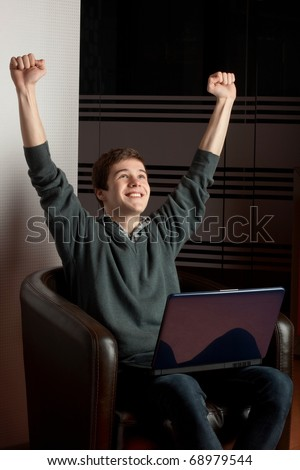 Young man raising his hands due to success - stock photo