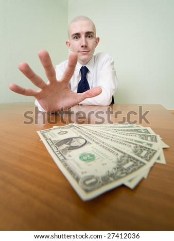 Young man reaches for a batch of money lying on a table - stock photo