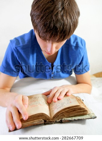 Young Man read the Old Book on the Bed at the Home - stock photo