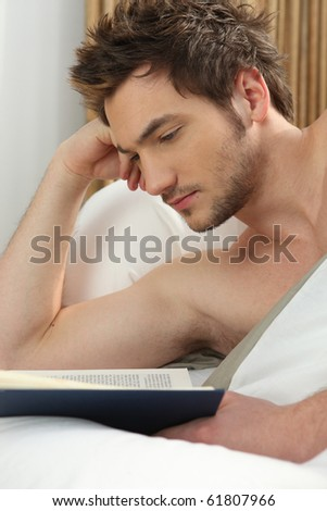Young man reading a book in bed - stock photo