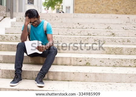 young man reading a letter in the street - stock photo