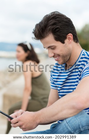 Young man reading an sms on his mobile phone and smiling at the content as he sits on a wall overlooking the ocean - stock photo