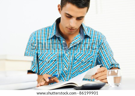 Young man reading and taking notes. - stock photo